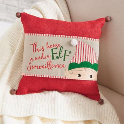 "Linen pillow wrap features an elf applique with ticking stripe santa hat with pom pom trim and printed phrase ""this house is under elf surveillance"" in red and green."